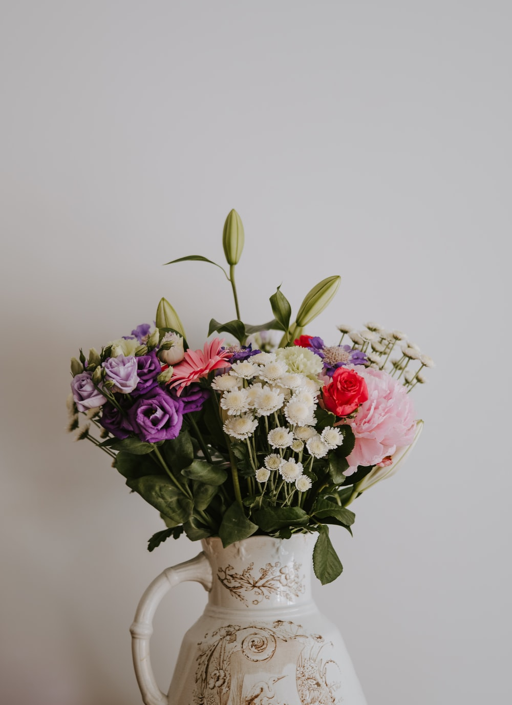 white, red, purple, and pink flowers on white ceramic vase