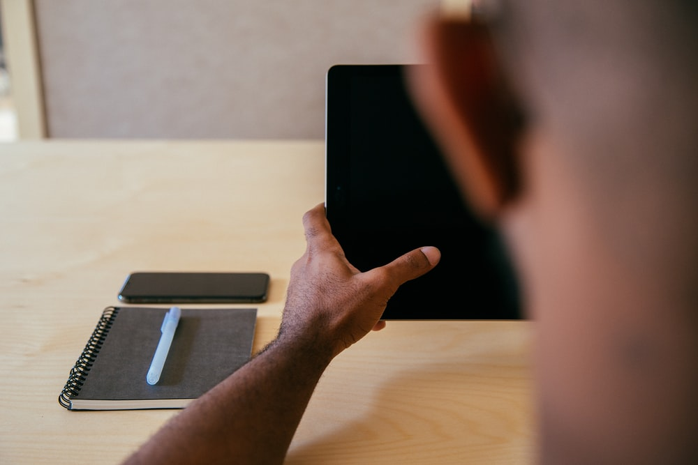 person holding black tablet computer