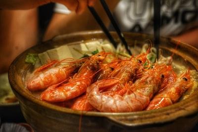 cooked shrimps on brown ceramic bowl lobster teams background