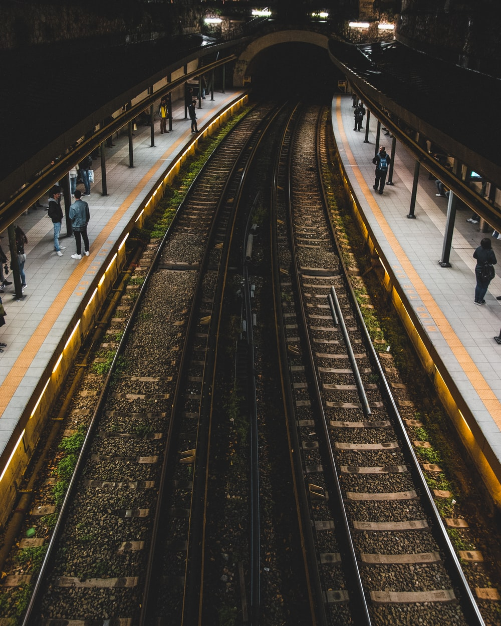 people standing beside train tracks