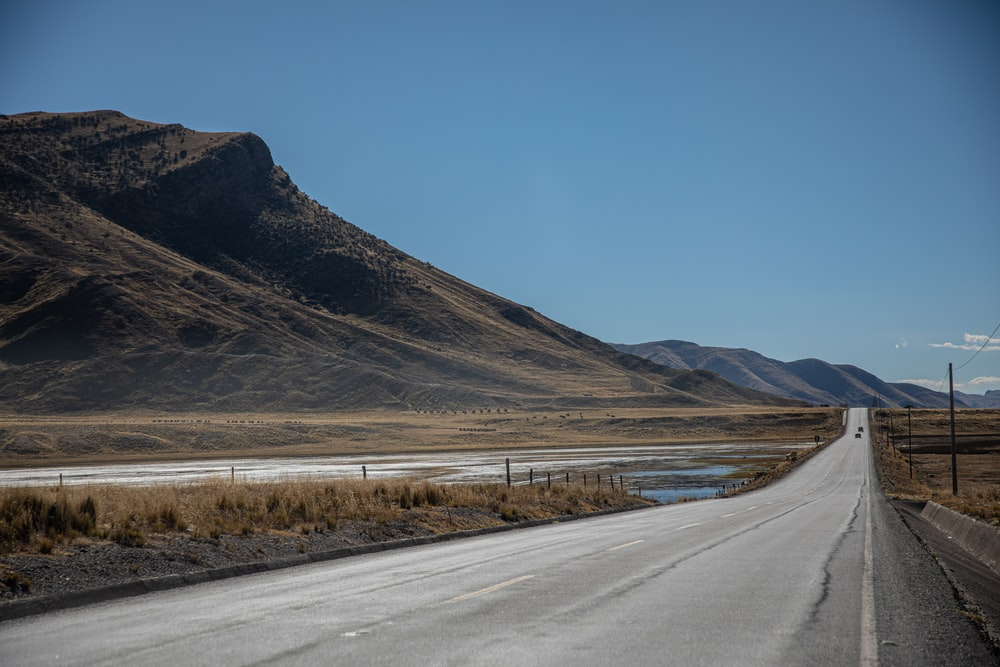 gray concrete road with no vehicle viewing mountain