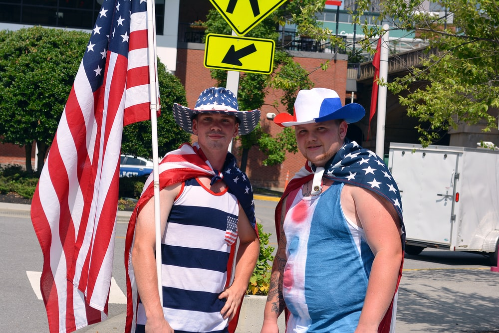 two men in tank tops holding USA flag
