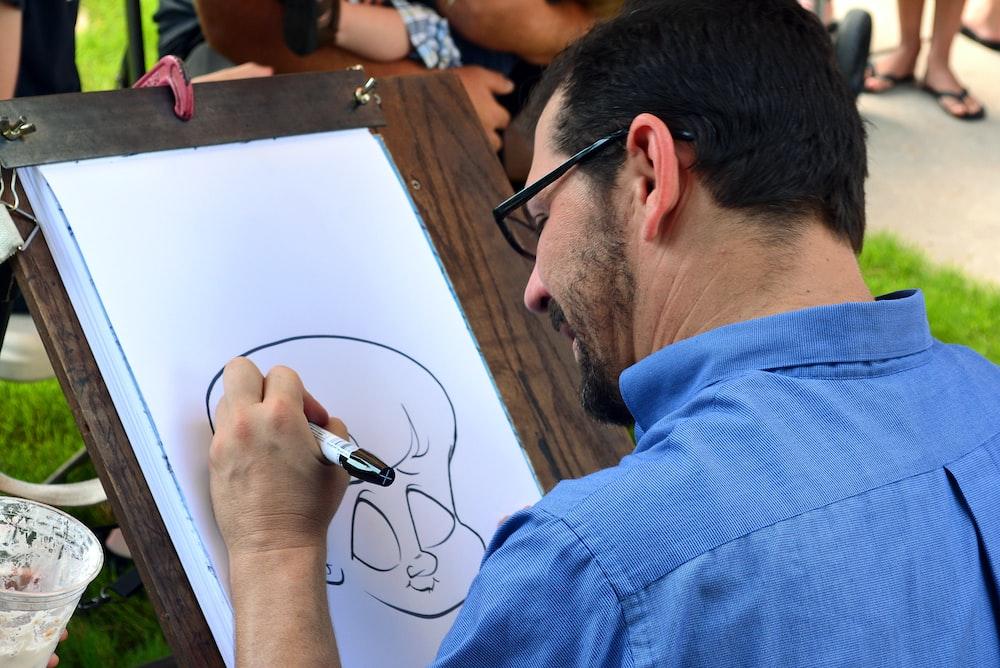 man in blue collared shirt sketching