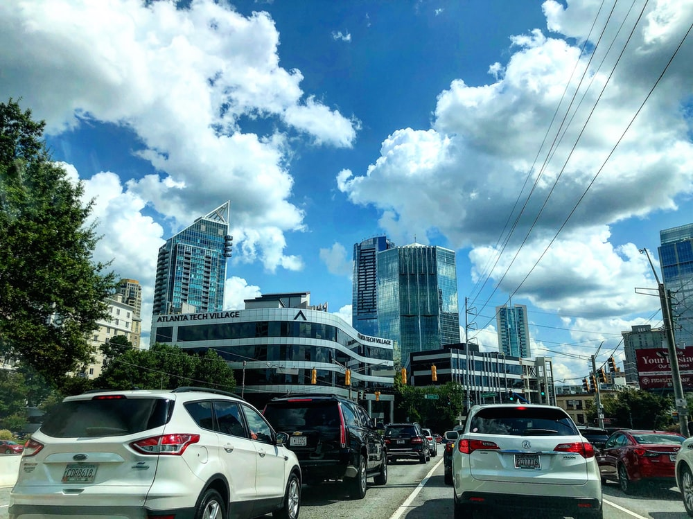 different vehicles on road viewing city with high-rise buildings under white and blue skies