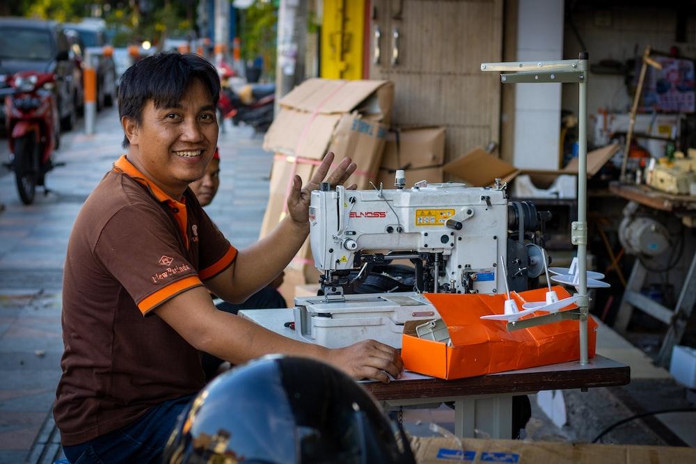 smiling man sitting beside sewing machine