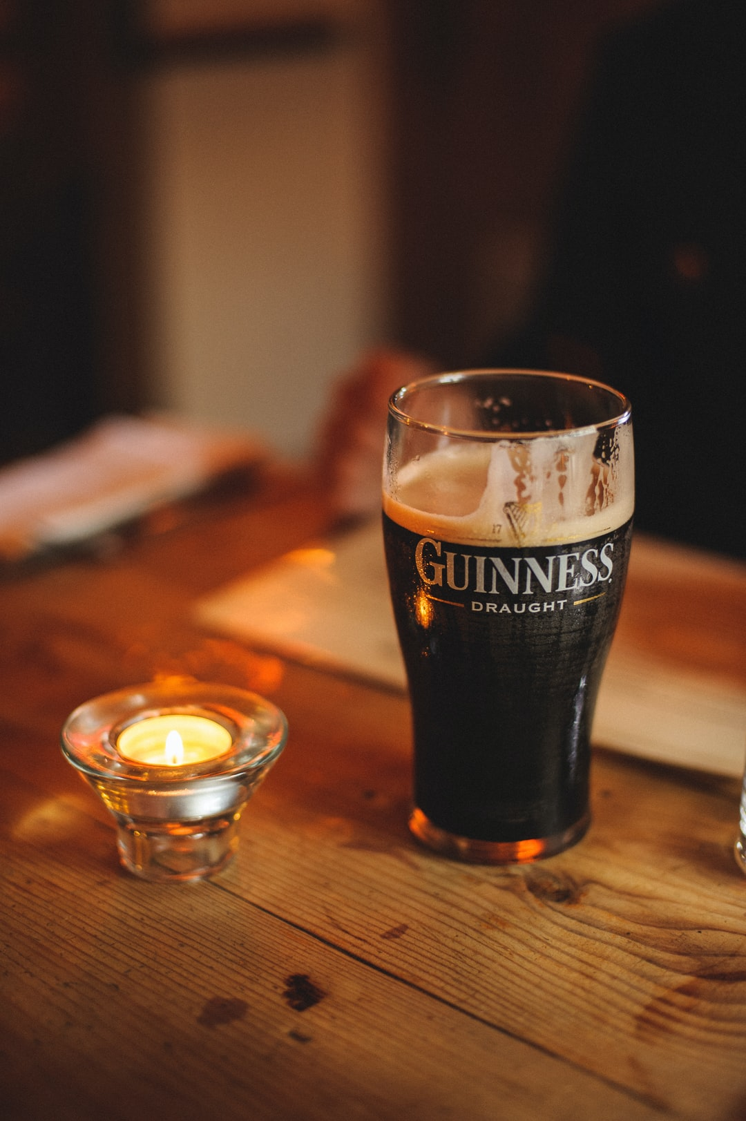 A Guinness Draught beer in a glass next to a candle in an English pub.