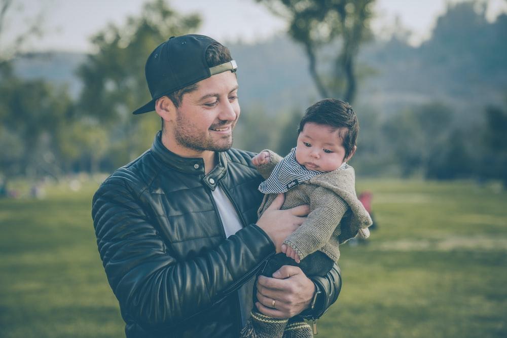 man wearing black leather jacket holding baby