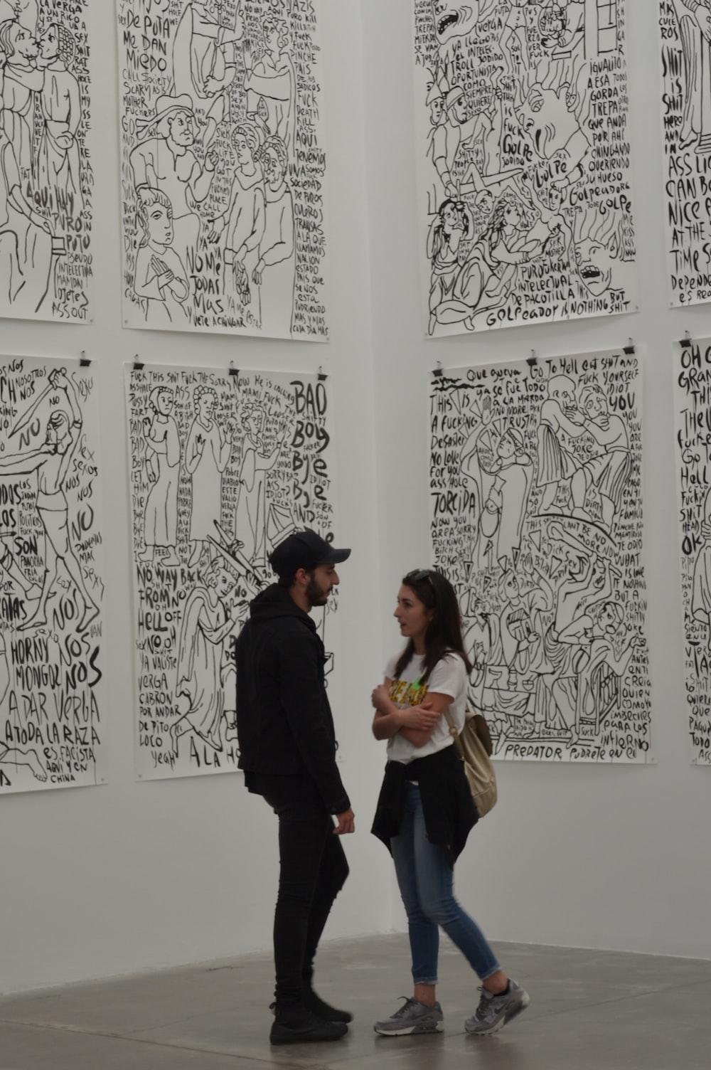 man wearing black cap talking to woman
