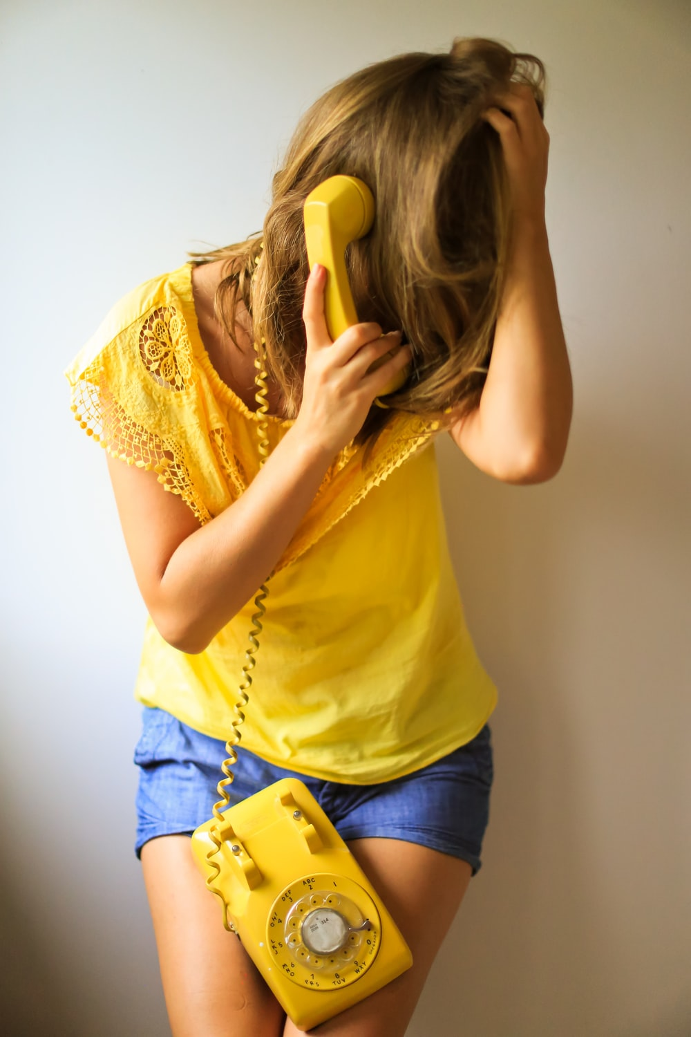 person in yellow T-shirt using rotary telephone
