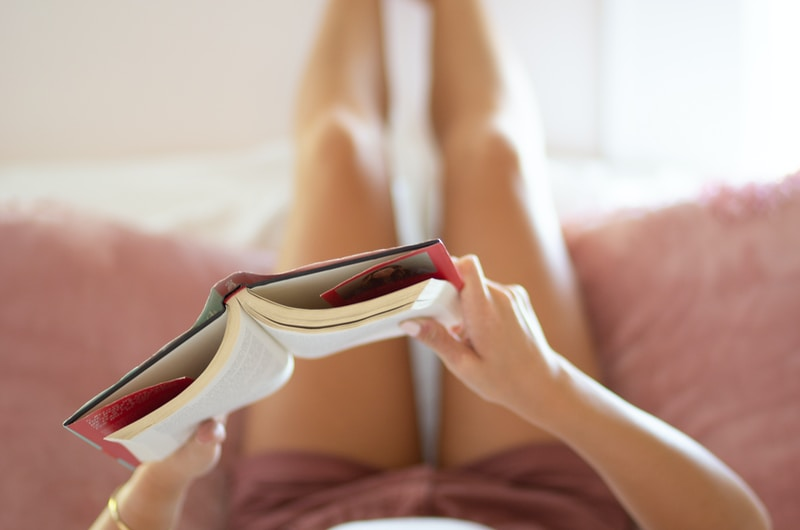woman holding book lying on bed close-up photography