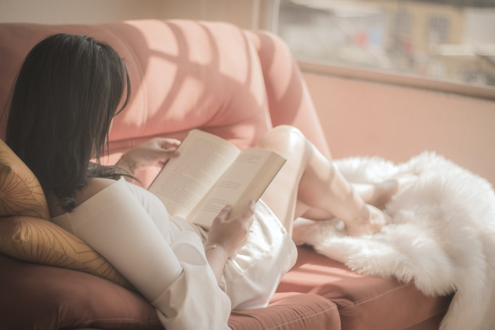 woman holding book sitting on pink fabric sofa