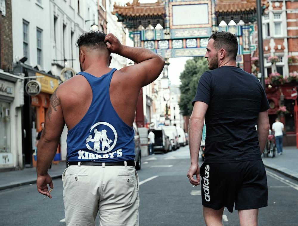 two men walking on road