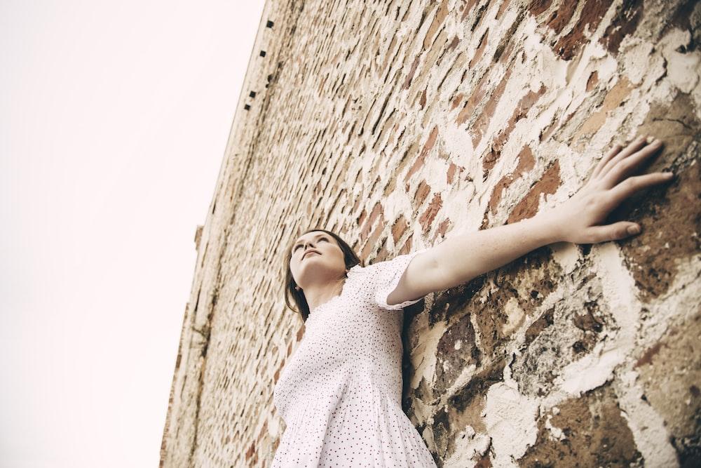 woman wearing white dress leaning on wall