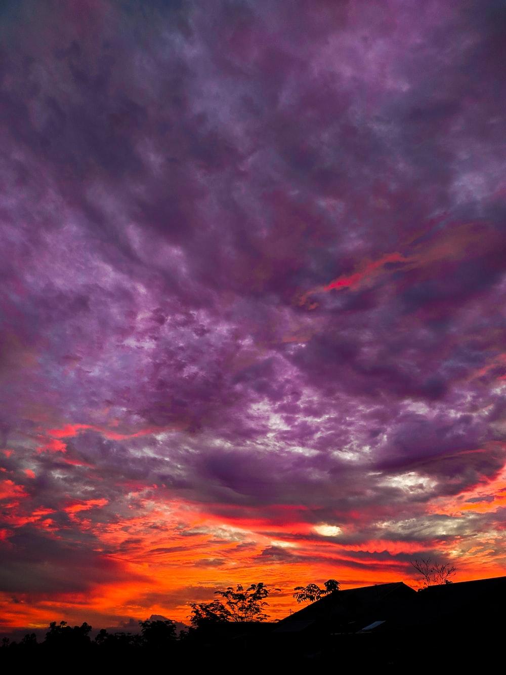 silhouette of mountain under purple and orange skies
