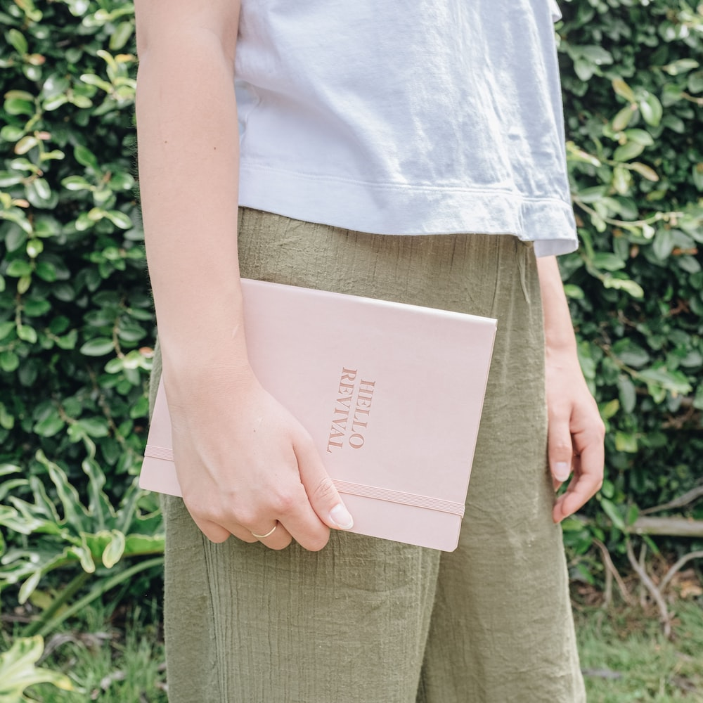 person in white shirt and brown pants carrying brown book