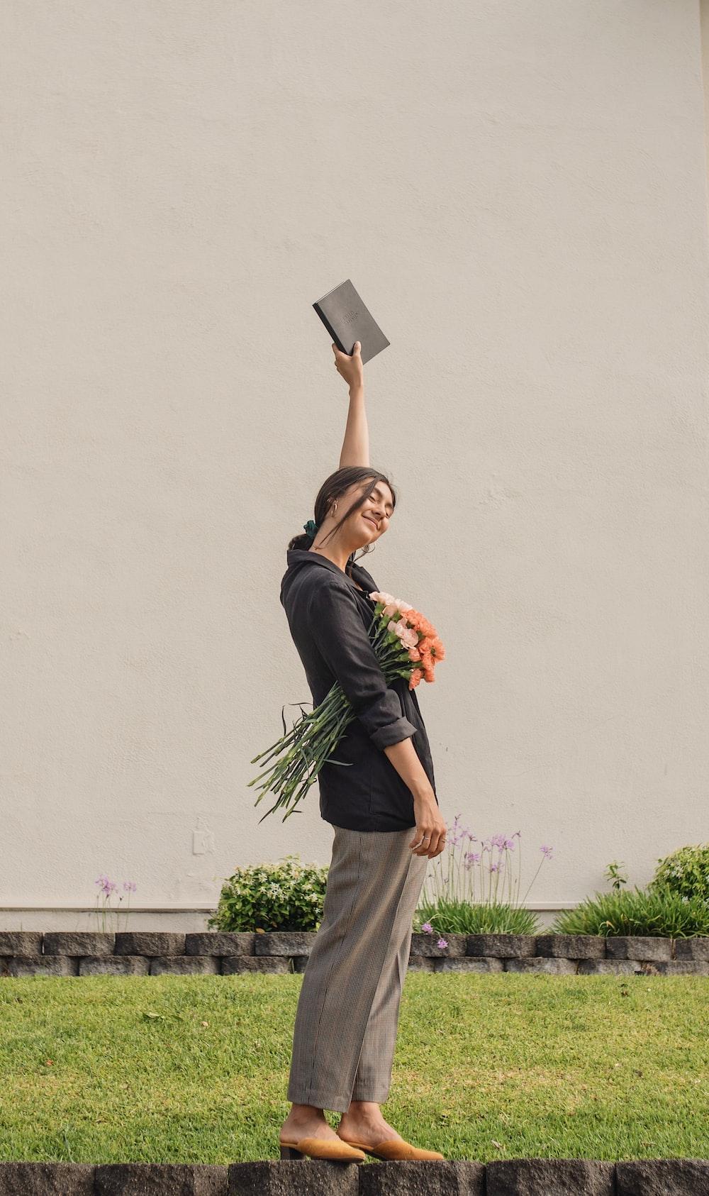 woman raising hand holding book