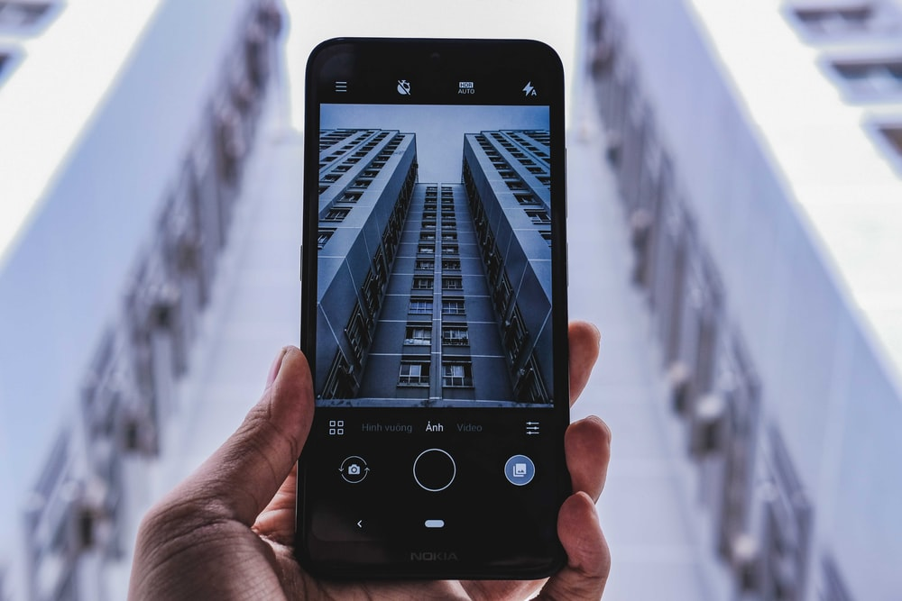 person taking photo of high-rise building