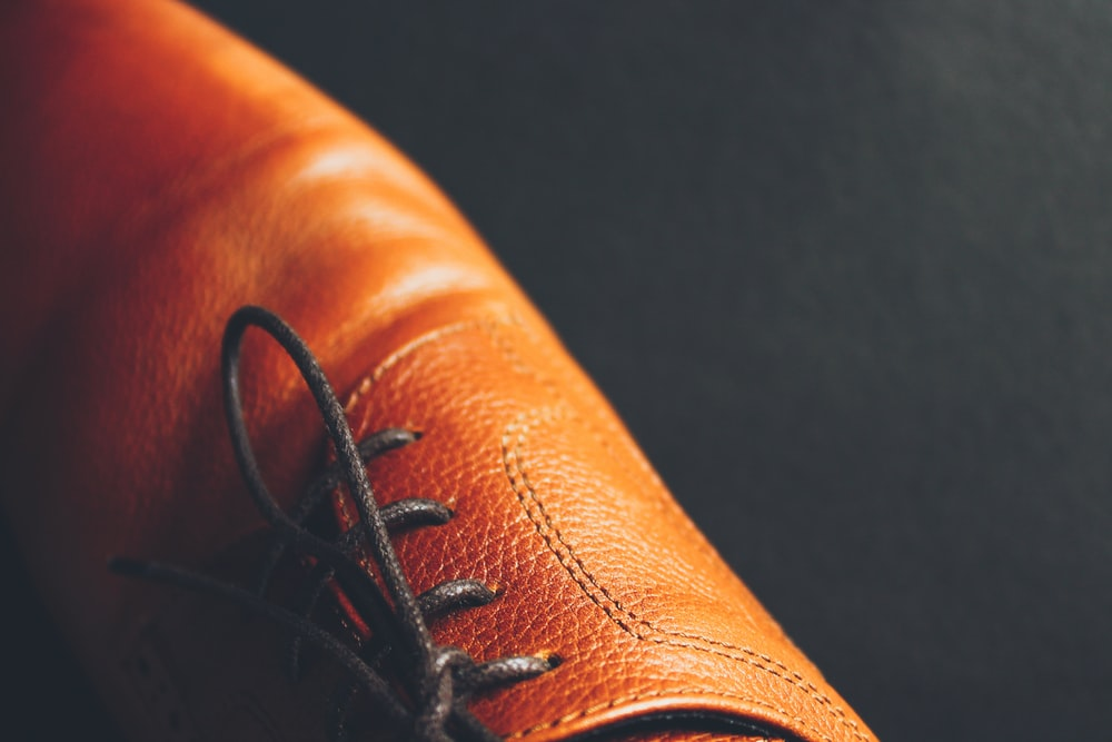 unpaired brown leather lace-up dress shoe