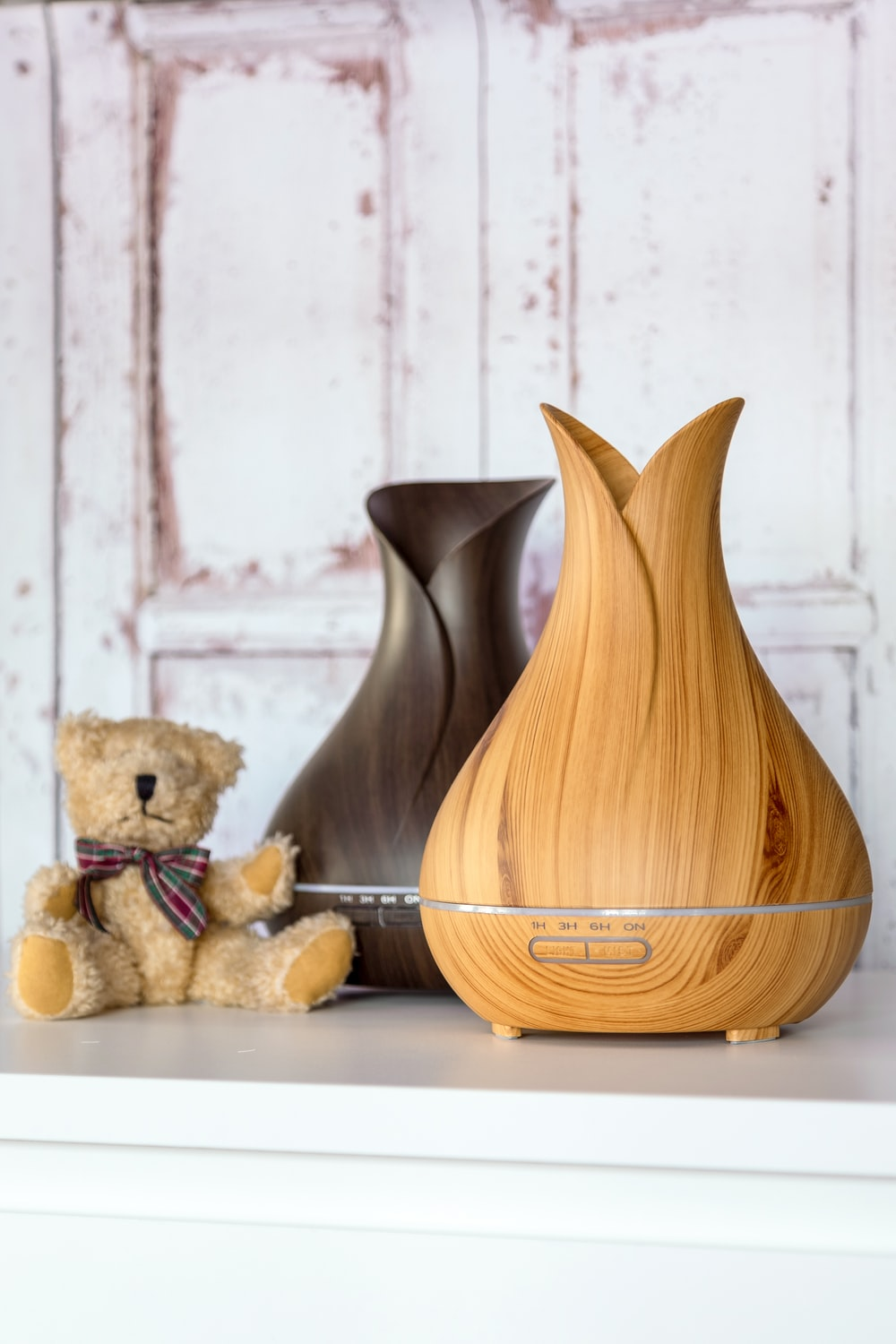 two brown diffusers beside plush toy