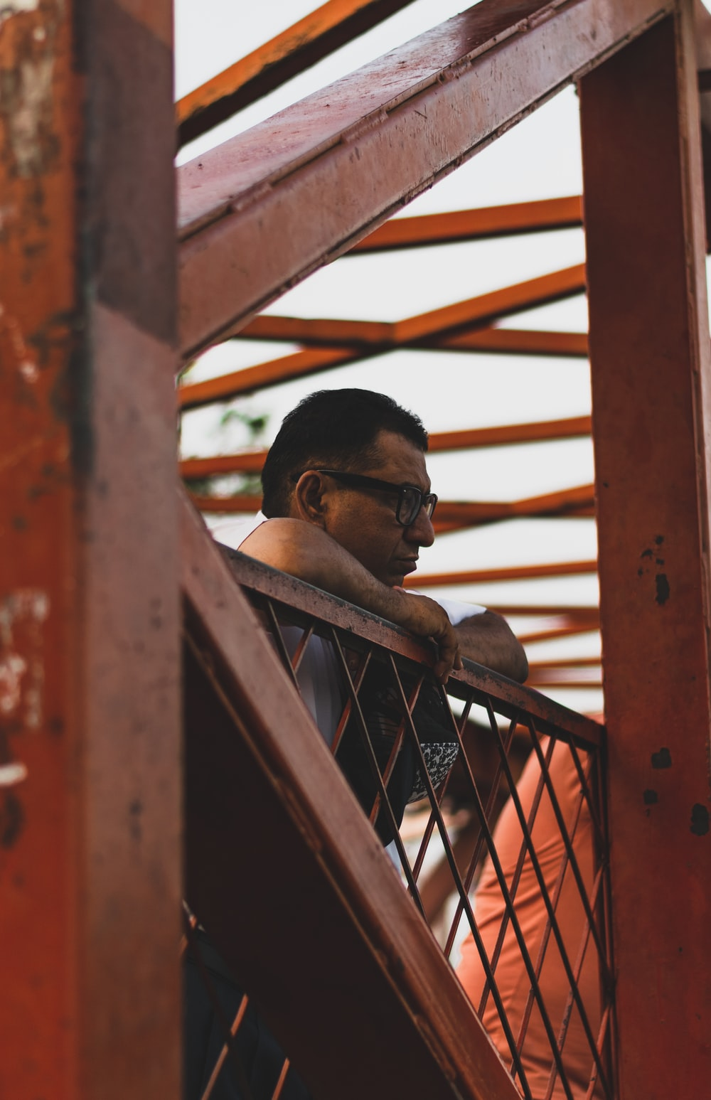 man standing near orange railings