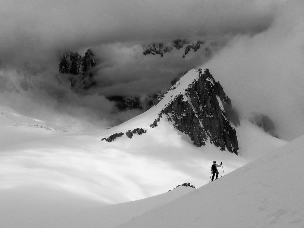 grayscale photography of man climbing on mountain