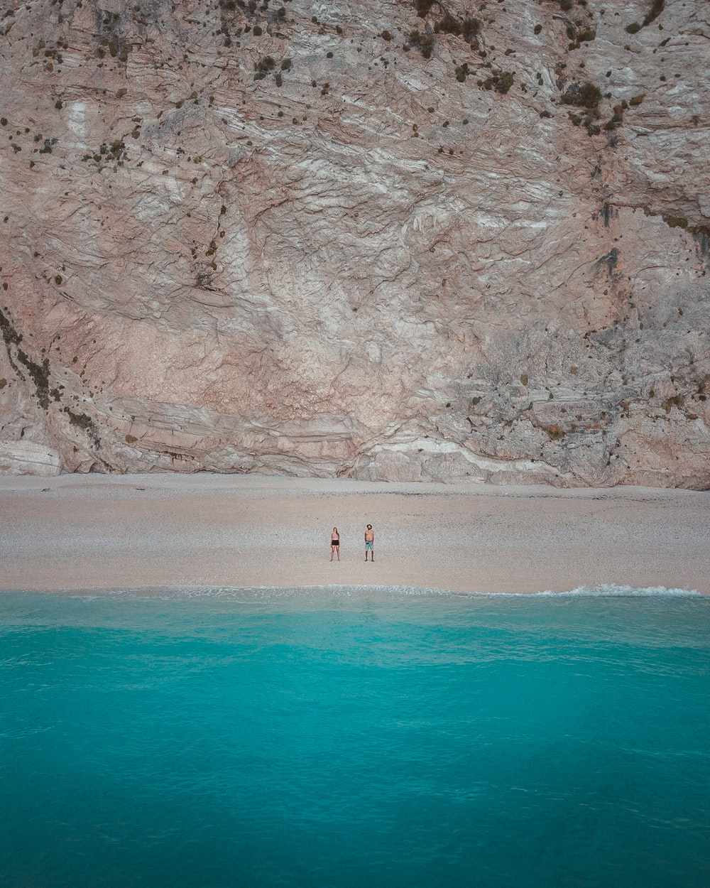 two people standing on shore near body of water