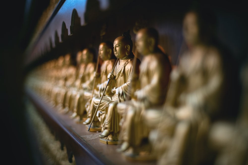 selective focus gold buddha sitting statue on the wall