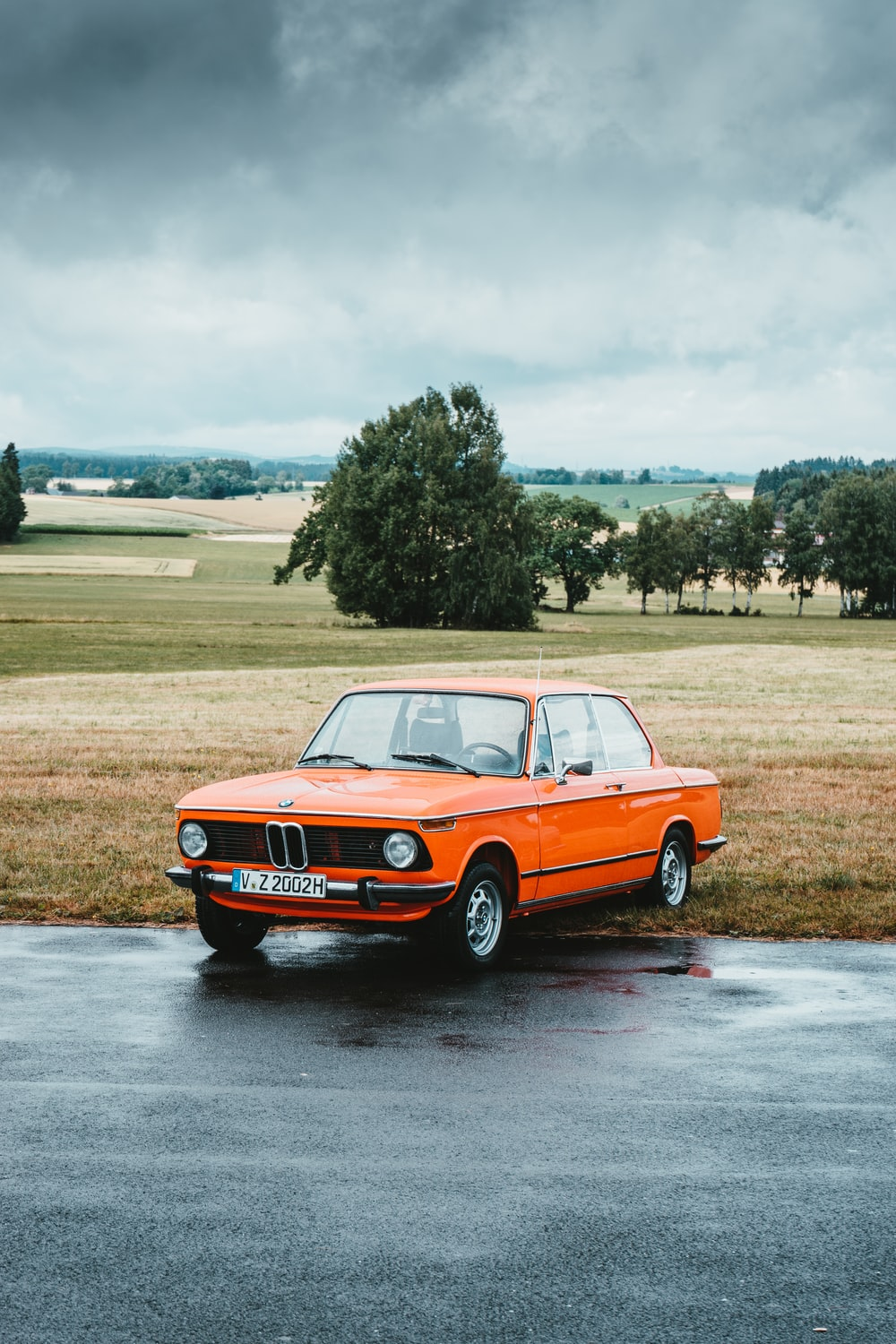 orange classic BMW coupe parked at roadside under grey cloudy sky