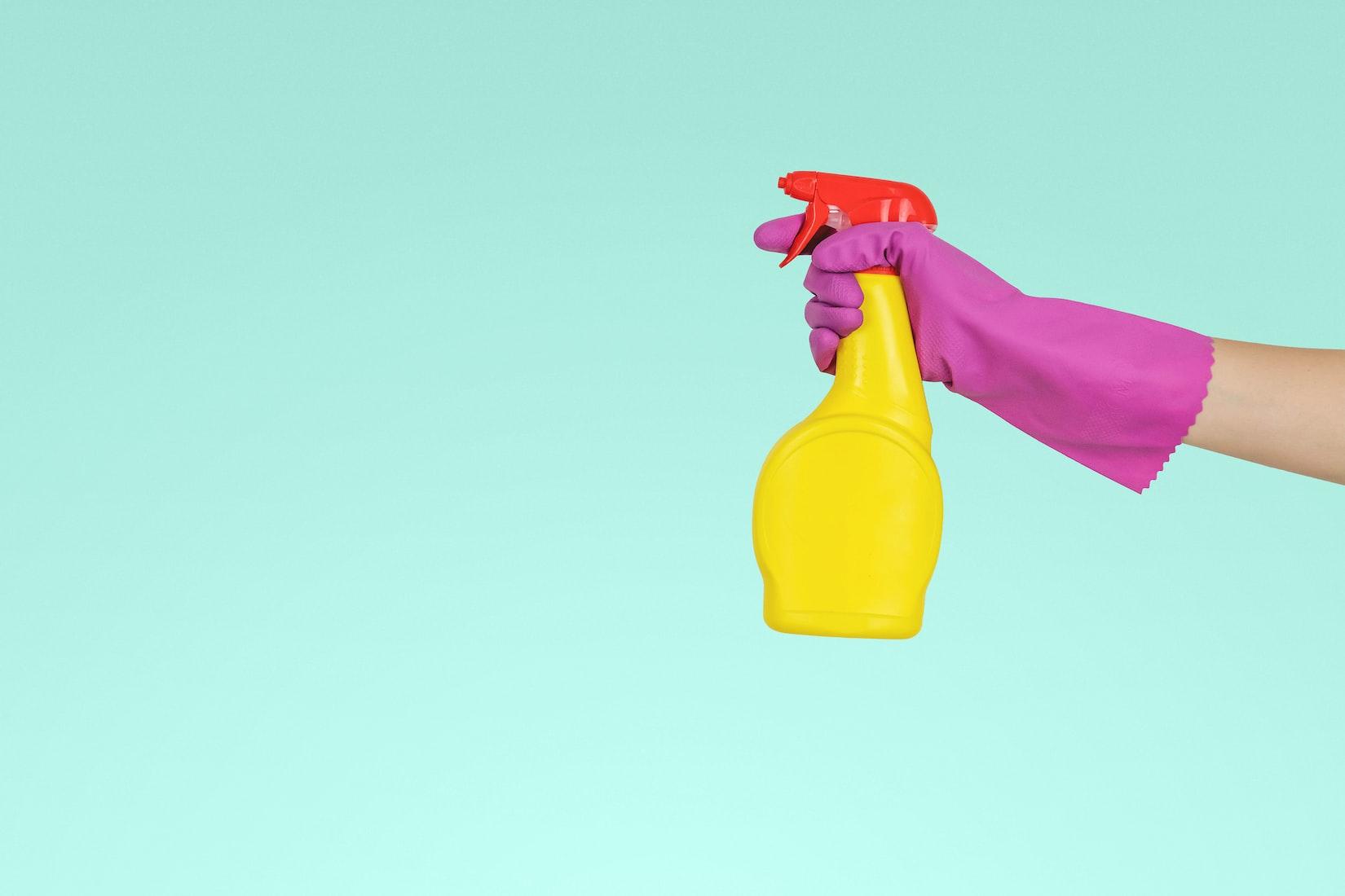 detalle de una mano con un guante que sostiene un spray para limpiar para ilustrar uno de los 7 regalos muy originales anti-estrés