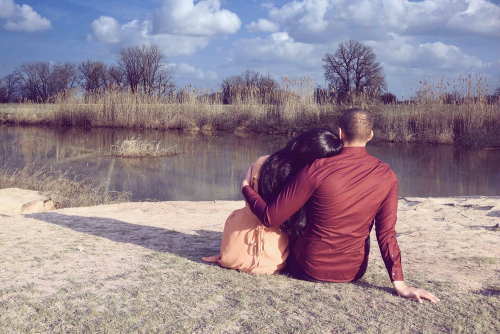 sitting man and woman overlooking at calm body of water during daytime