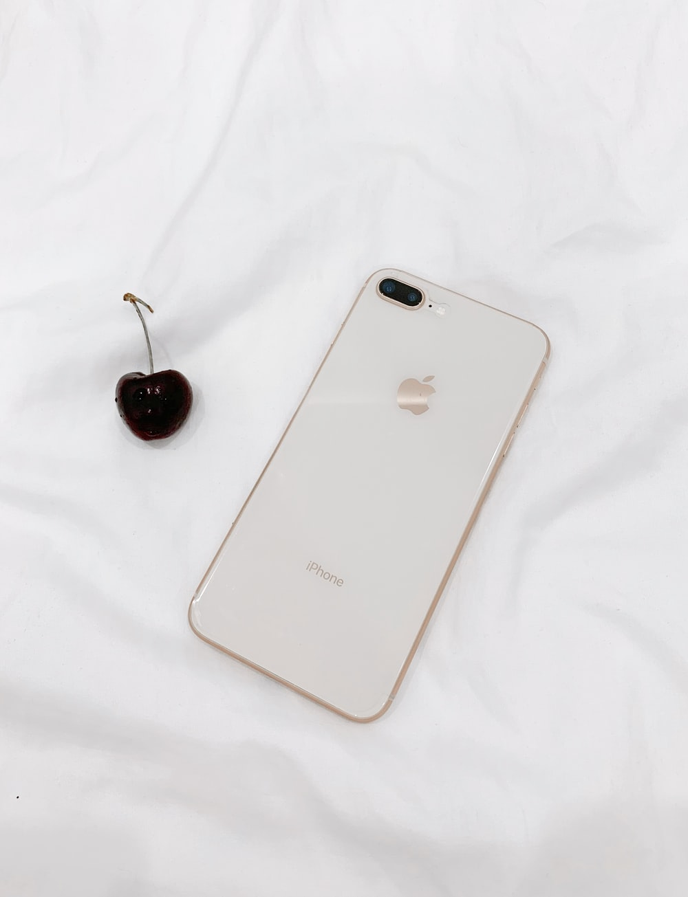 white iPhone 8 and red cherry fruit