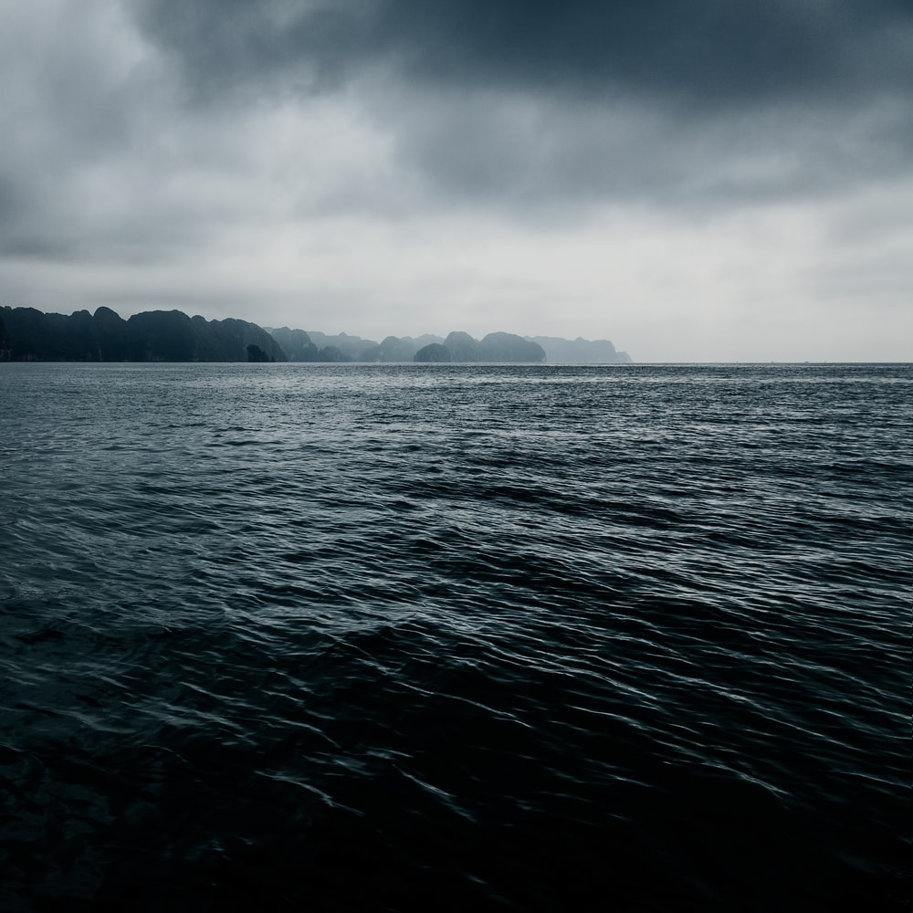 body of water under gray clouds at daytime