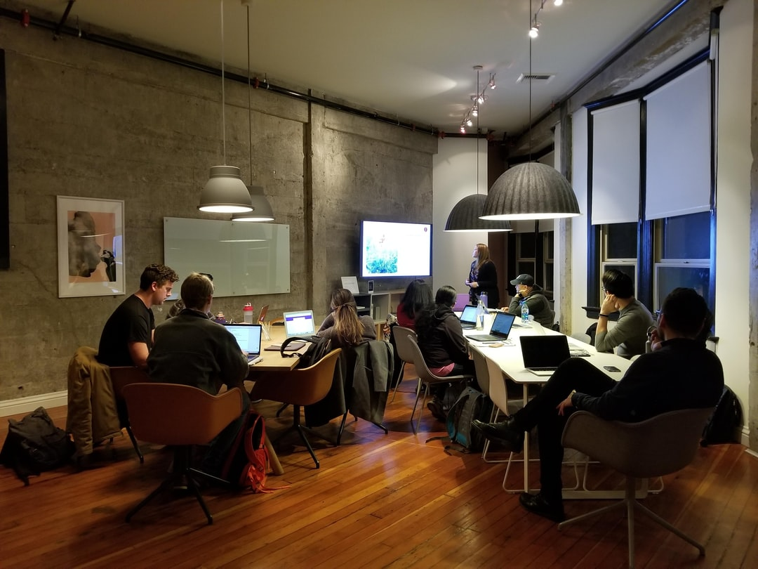 group of adult students sitting at a large table working on computers and discussing