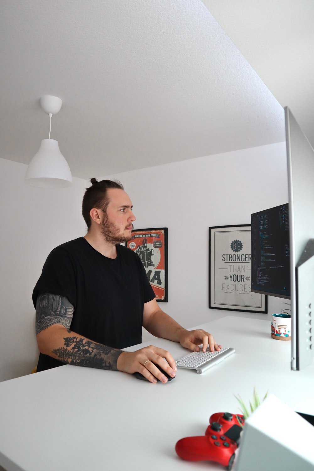 standing man wearing black crew-neck t-shirt holding mouse and keyboard