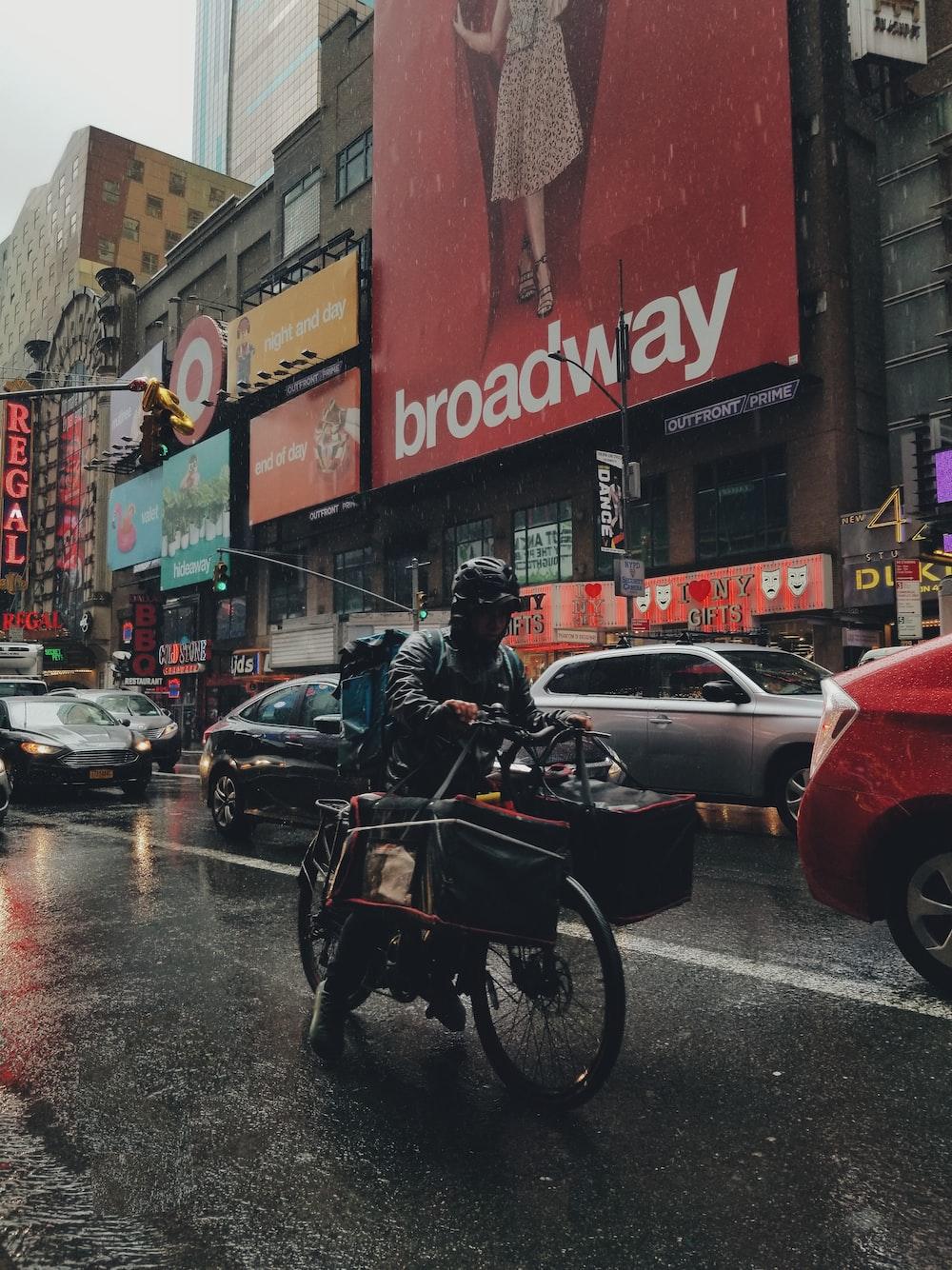 man riding bicycle in road during daytime