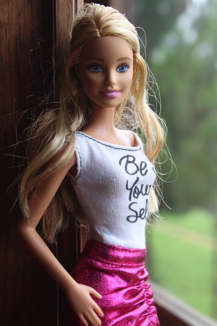 Blonde Barbie wearing the color pink (skirt) and smiling.