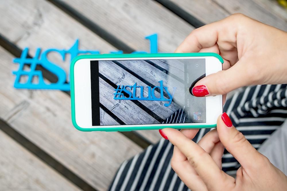 woman using white smartphone taking photo