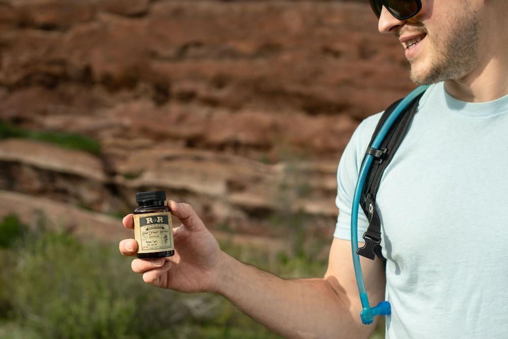 man holding brown and black RR medication jar