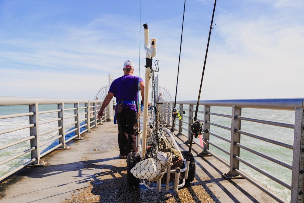 man fishing in dock during daytime