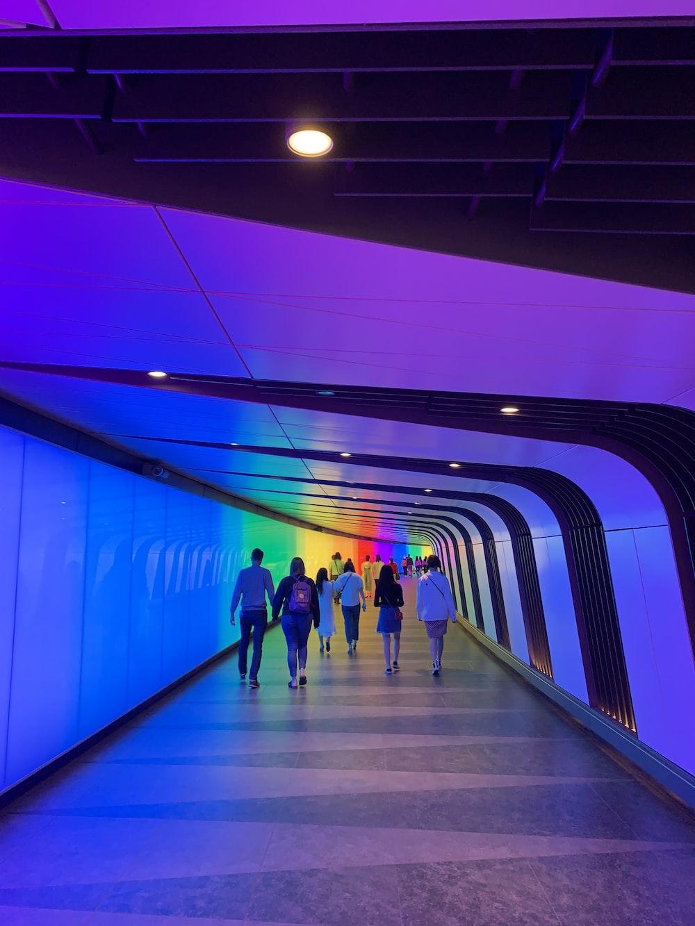 people walking on purple hallway