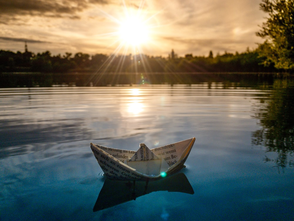 white paper boat on calm body of water during dayti,e