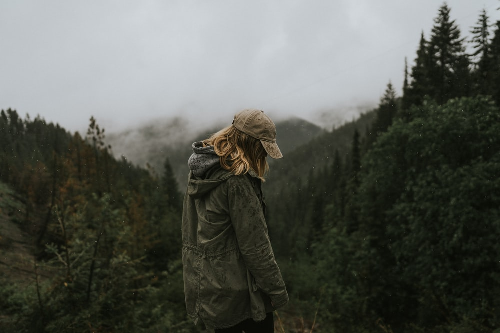 woman in gray coat standing on forest