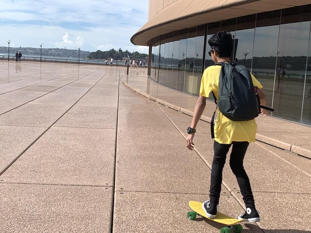 boy riding yellow skateboard during daytime