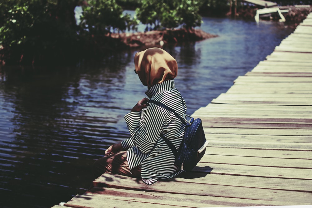 person with backpack sitting on dock