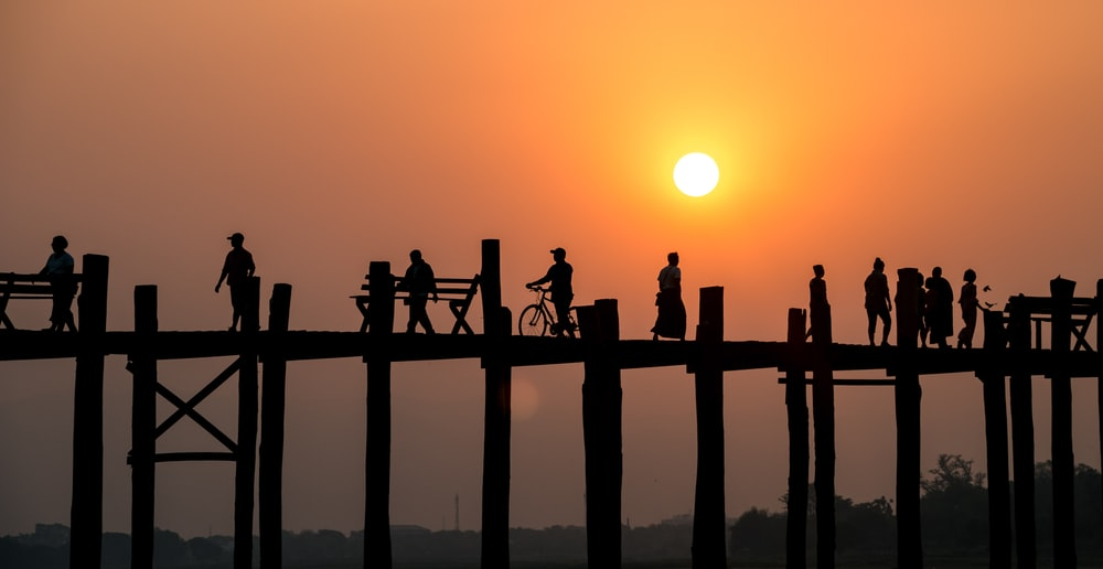 silhouette of people on bridge