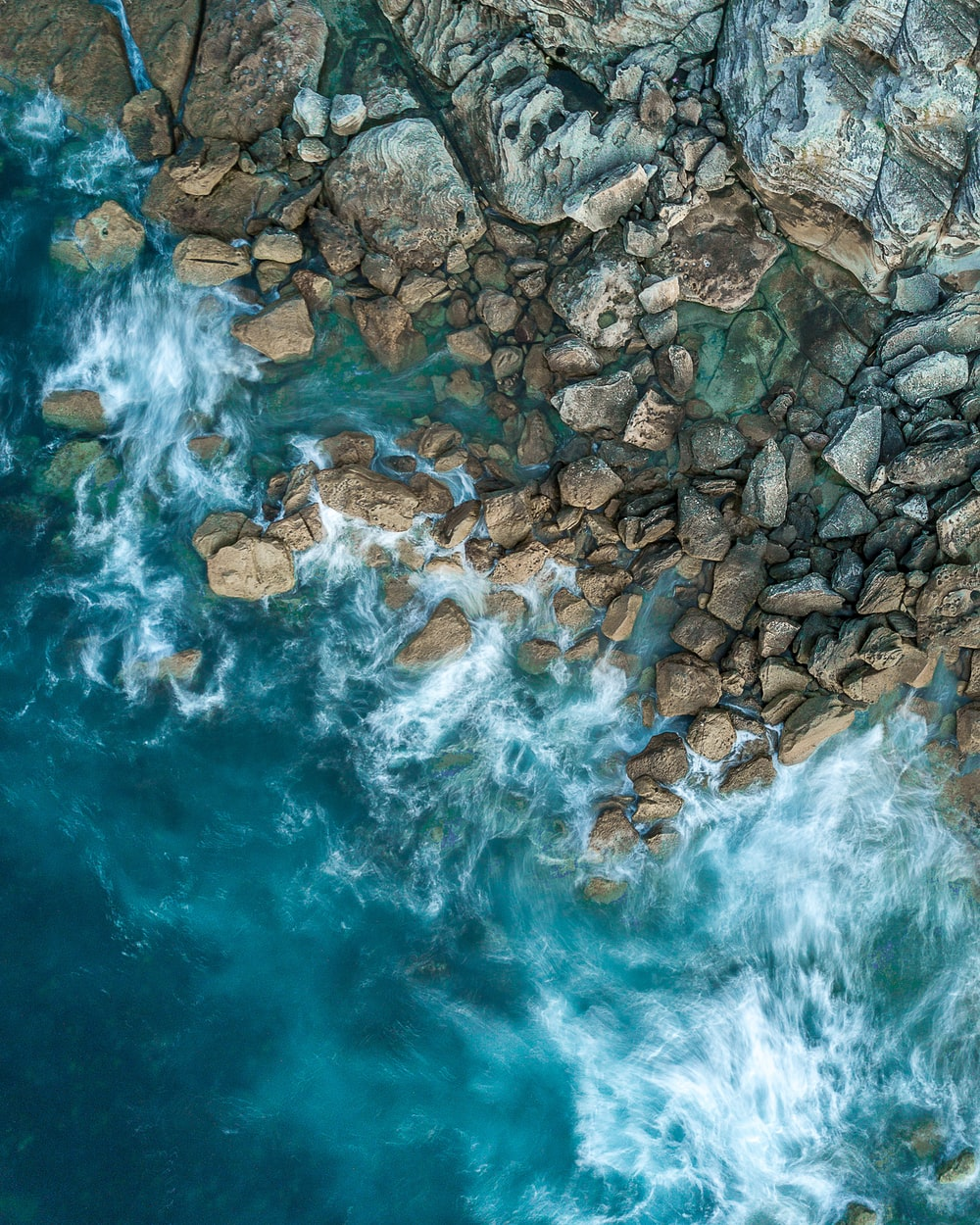 top-view photography of sea and rock formation during daytime