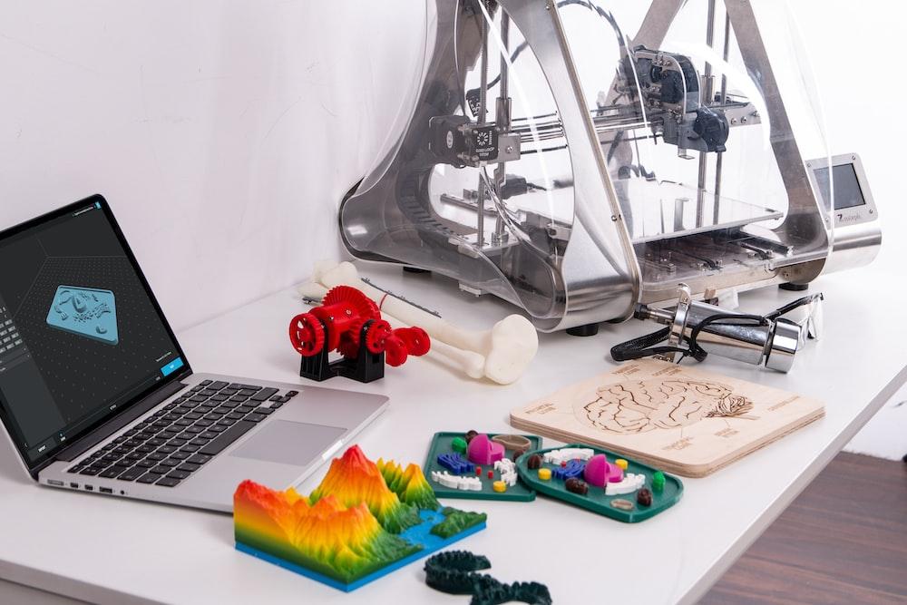 MacBook Pro beside 3D printer