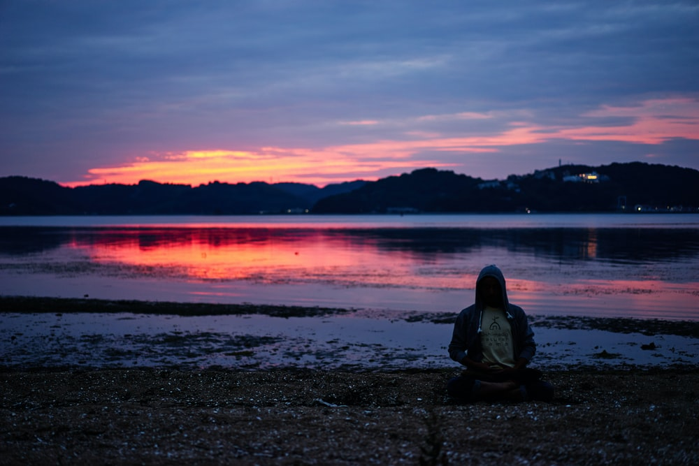 man sitting in lotus position on beach at sunset