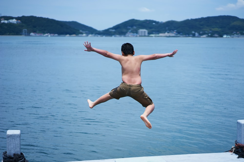 kid jumping from a dock to body of water during daytime