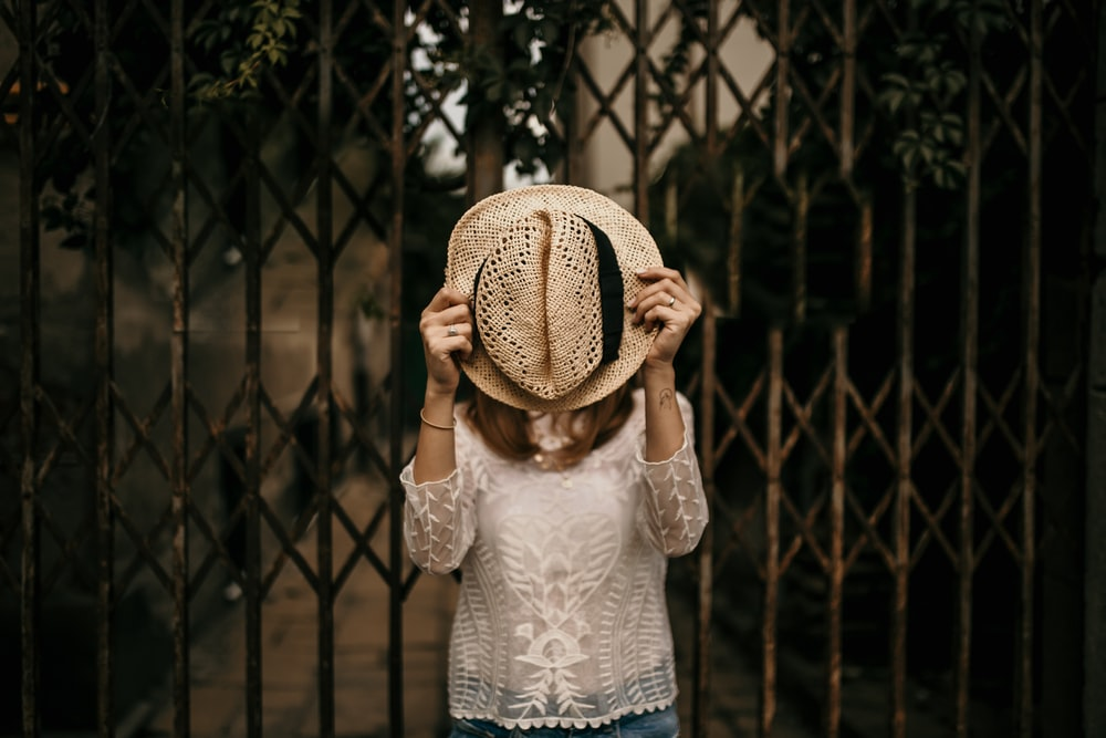 woman in white floral lace long sleeved shirt holding up brown straw hat